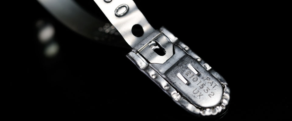The patented locking mechanism features inspection holes to confirm positive locking while crimped and folded edges show evidence of physical intrusion into the locking box.