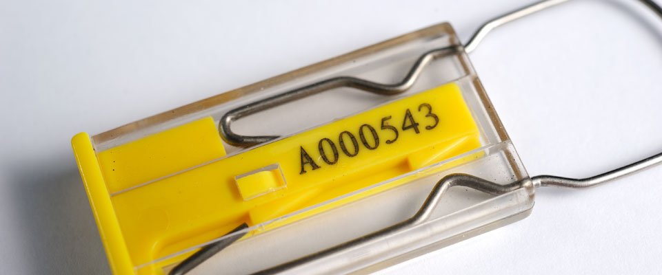 Laser engraved printing is protected by a clear encapsulation which also serves as a window into the locking mechanism so that it can be inspected for security.
